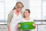 Daughter holding recycling box with her mother