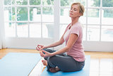 Mature woman doing yoga on fitness mat