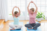 Mother and daughter doing yoga on fitness mat