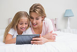 Mother and daughter using tablet together on bed