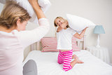 Mother and daughter having pillow fight