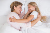 Mother and daughter cuddling in bed