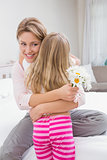 Mother and daughter hugging with flowers