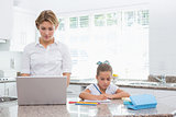 Little girl doing her homework with mother using laptop
