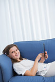 Little girl using digital tablet on the couch