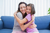 Mother and daughter hugging on couch