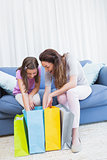 Mother and daughter looking at shopping bags