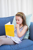 Little girl reading on couch