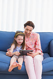 Mother and daughter using tablet on couch