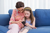 Mother and daughter using smartphone on couch