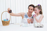 Mother and daughter painting easter eggs