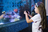 Cute girl looking at fish tank