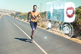 Composite image of athletic man jogging on open road with monitor around chest