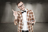 Composite image of geeky hipster holding a tablet pc