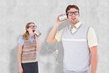 Composite image of geeky hipster couple speaking with tin can phone