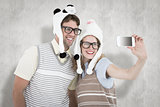 Composite image of geeky hipster couple taking selfie with smartphone