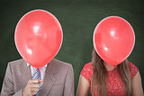 Composite image of geeky couple holding balloons in front of their faces