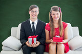 Composite image of cute geeky couple smiling and holding gift