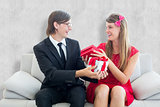 Composite image of cute geeky couple smiling and offering gift