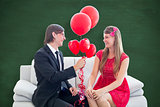 Composite image of cute geeky couple with red balloons