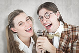Composite image of happy geeky hipsters singing with microphone