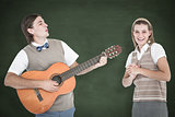 Composite image of geeky hipster serenading his girlfriend with guitar