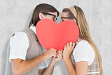 Composite image of geeky hipsters kissing behind heart card
