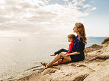 Mother and daughter sitting on a rock near the sea