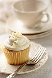 Closeup of vanilla cupcake with tea cup