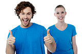 Cheerful couple holding thumbs up