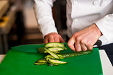 Chef chopping leek over green carving board