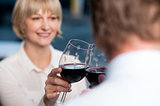 Blur images of couple raises a glass of red wine