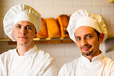 Young smiling chefs posing in bakery