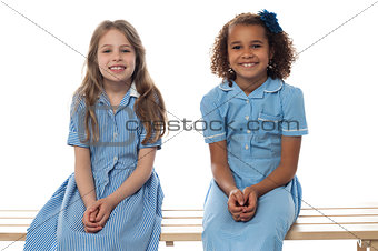 Cheerful kids relaxing on school bench