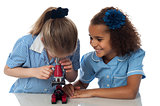 Little girls looking into microscope