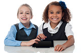 Smiling school girls playing on touchpad