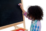 Young school child writing on blackboard