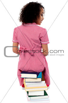 Back pose of a girl sitting on a pile of books