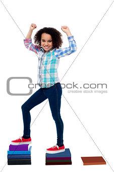 Active girl kid climbing on notebooks