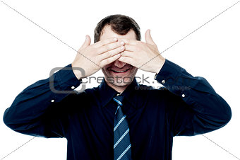 Smiling businessman put his hands over eyes