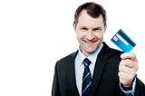 Smiling businessman holding credit card