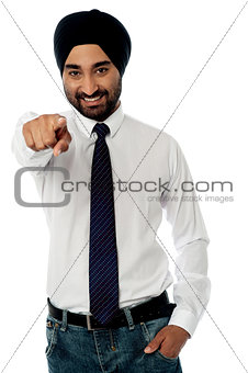 Smiling businessman pointing towards you
