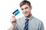 Smiling corporate guy showing his debit card