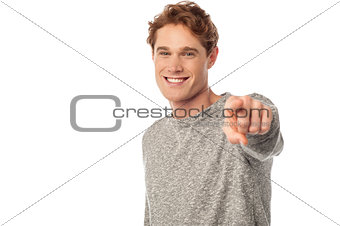 Smiling young man pointing you out