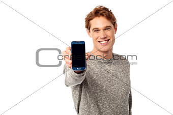 Young man displaying brand new cellphone