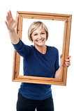 Excited woman holding picture frame