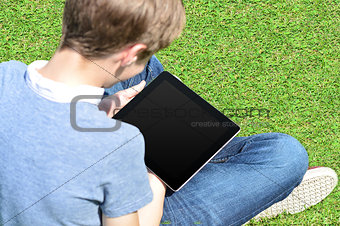 Boy with crossed legs relaxing outdoors