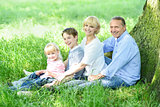 Cheerful family resting under tree