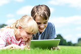 Two children lying down and using tablet pc