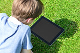 Young boy using digital tablet outdoors
